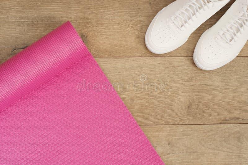 Rosa Yogamatte und weiße modische Turnschuhe auf einem hölzernen Hintergrund Eignungskonzept, aktiver Lebensstil, Körperpflegekon stockfotos