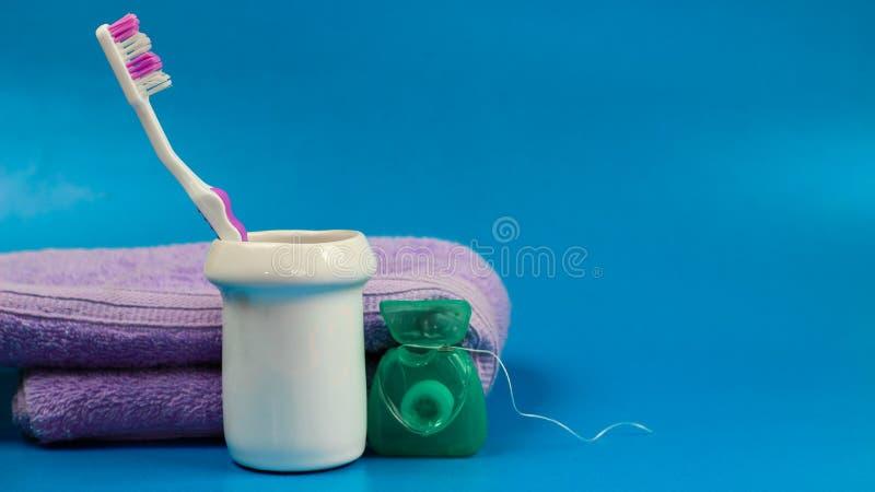Rosa Zahnbürste mit Zahnseide, in der weißen Schüssel lizenzfreies stockfoto