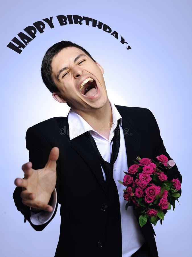 Rosafarbene Blume der stattlichen romantischen Holding des jungen Mannes lizenzfreies stockfoto