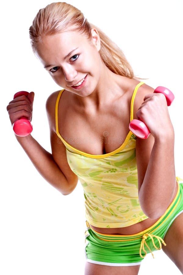 Rosafarbene Dumbbells in den Händen der Frauen lizenzfreies stockbild