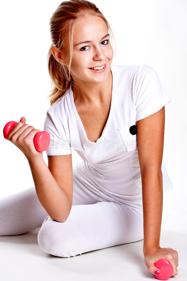 Rosafarbene Dumbbells in den Händen der Frauen lizenzfreie stockfotos