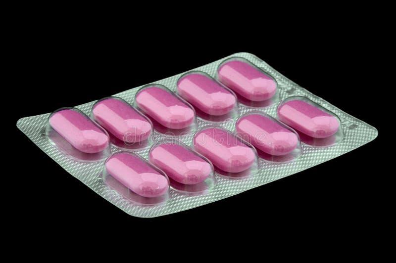 Rosafarbene Pillen auf Schwarzem stockbilder