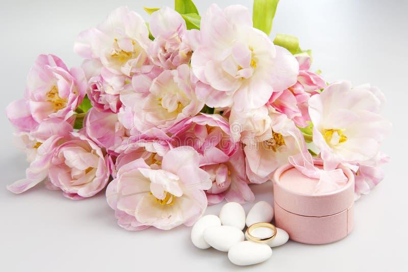 Rosafarbene Tulpen und Hochzeitsringe stockfotografie