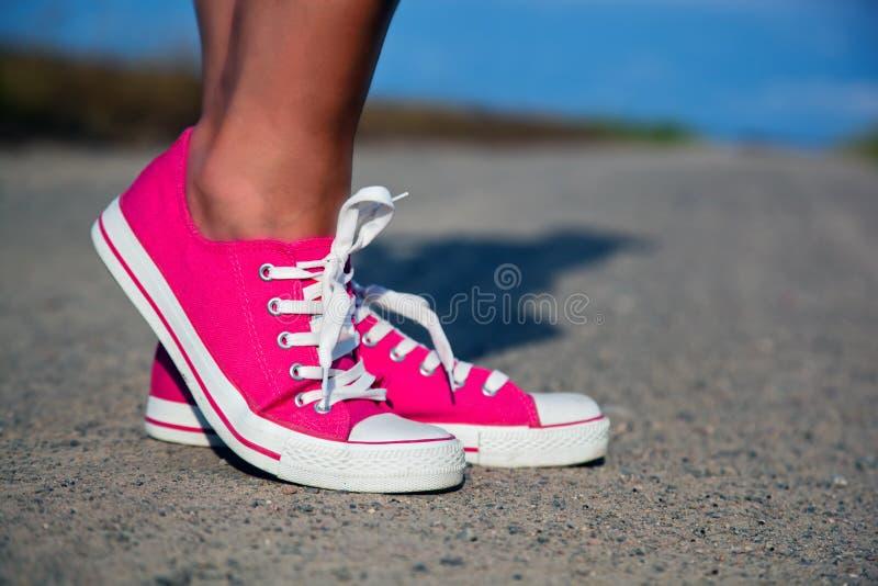 Rosafarbene Turnschuhe auf Mädchenfahrwerkbeinen lizenzfreies stockfoto