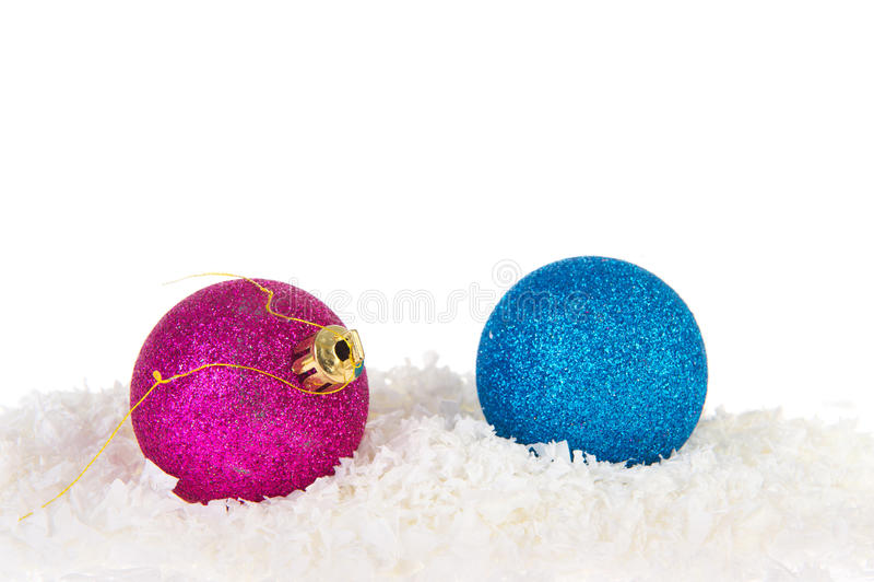Rosafarbene und blaue Weihnachtskugeln im Schnee stockfotos