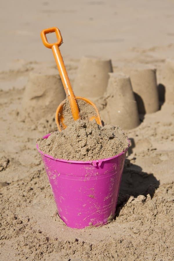 Rosafarbene Wanne und orange Spaten im Sand lizenzfreie stockfotos