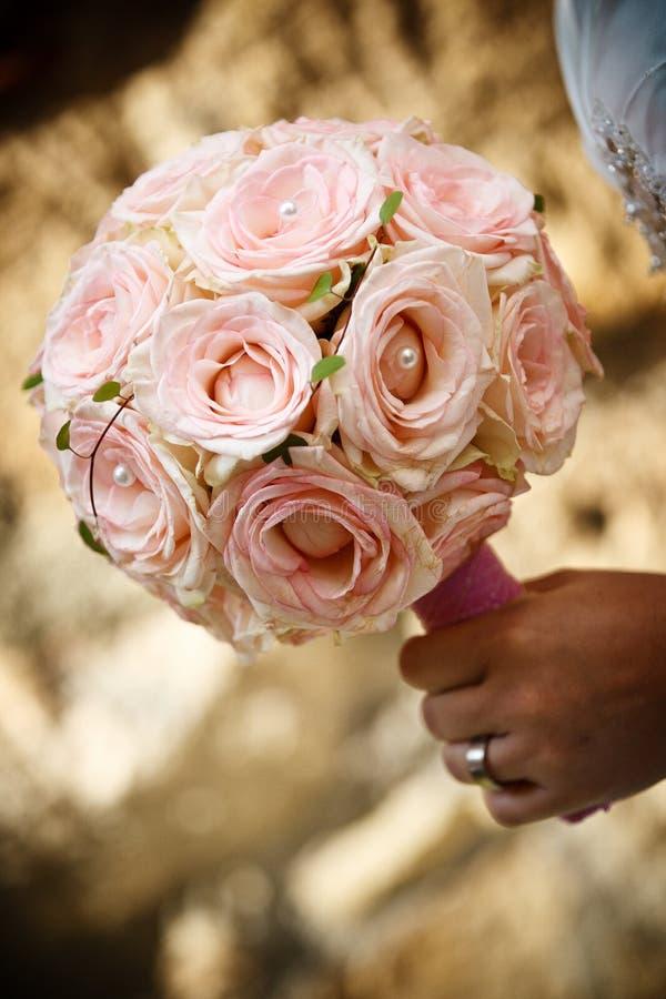 Rosafarbener Blumenstrauß in der Brauthand lizenzfreie stockfotos