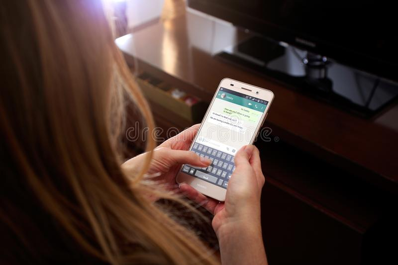 ROSARIO, ARGENTINA - 30 DE MAIO DE 2018: Menina com smartphone em suas mãos e em uma conversação do whatsapp na tela Jovem mulher imagens de stock royalty free
