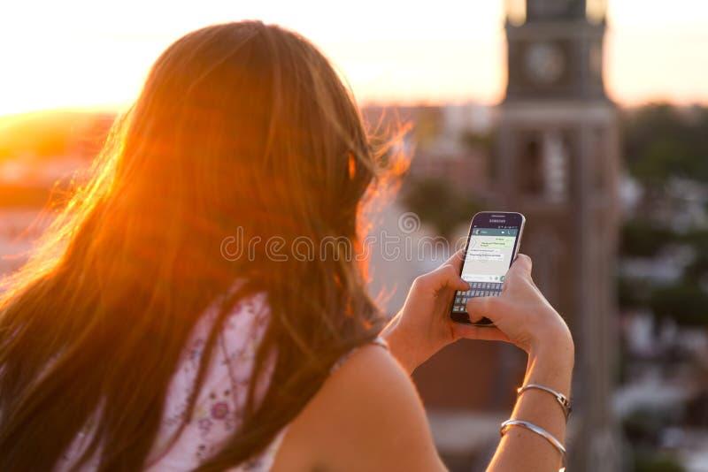 ROSARIO, ARGENTINA - 8 NOVEMBRE 2017: Ragazza al tramonto con lo smartphone nelle sue mani ed in una conversazione del whatsapp s immagini stock libere da diritti