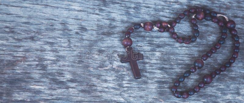 Rosario ascendente cercano en fondo de madera como símbolo de la salvación y de la vida eterna imagen de archivo libre de regalías