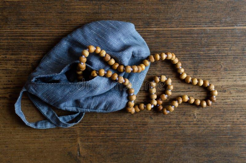 Rosario de madera Rosario de madera en un bolso azul en un piso de madera fotos de archivo libres de regalías
