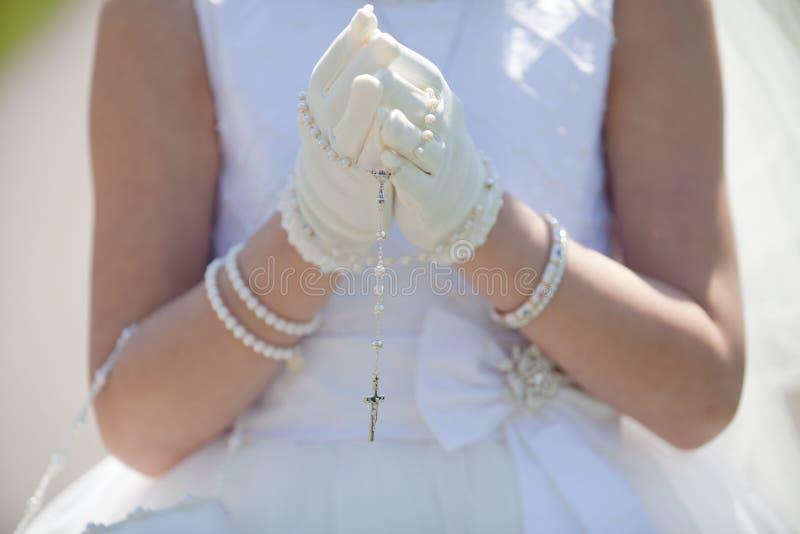 Rosary εκμετάλλευσης νέων κοριτσιών γύρω από τα φορημένα γάντια χέρια της που είναι στην προσευχή στοκ εικόνα