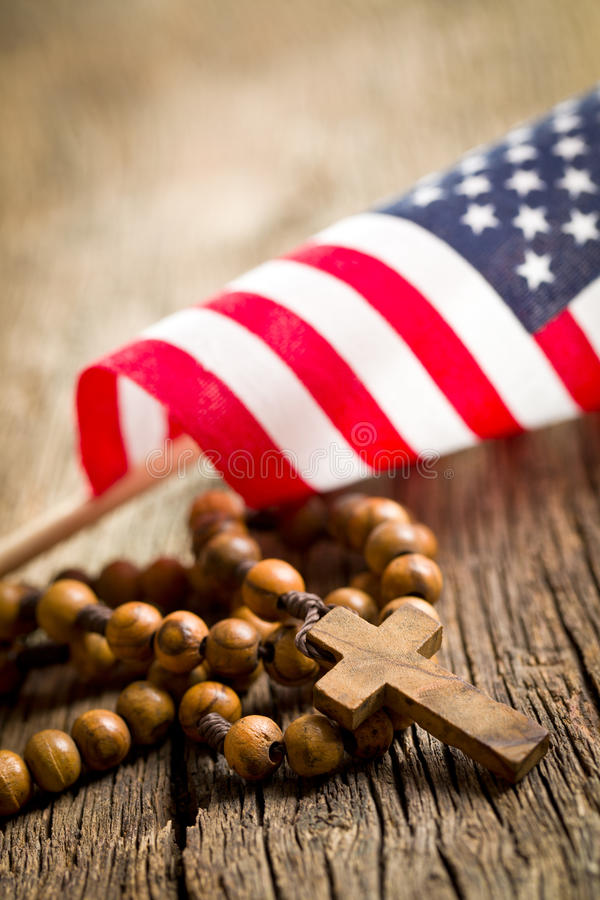 Rosary beads with american flag. On wooden background stock image