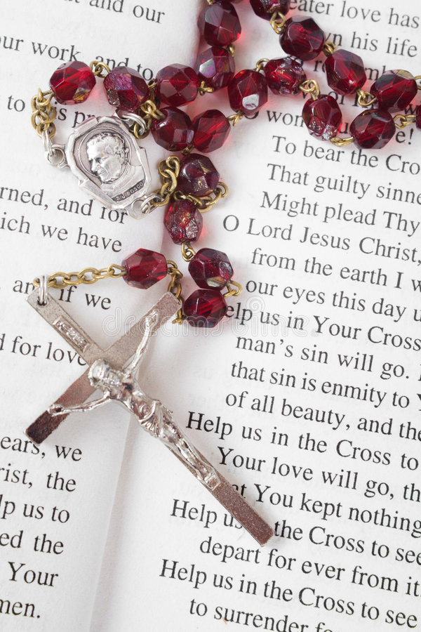 Rosary beads on a book of psalms. Closeup of rosary beads on an open book of psalms royalty free stock photography