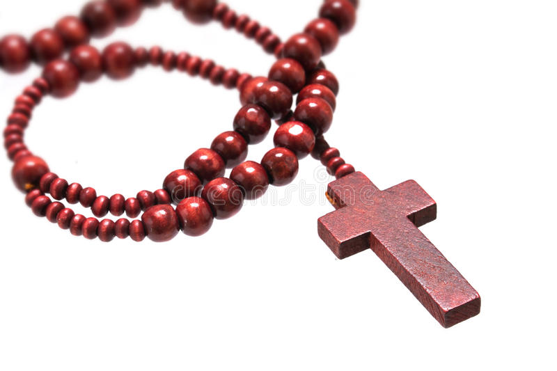 rosary beads with cross made of red wood isolated on a white background, close up with selected focus on christ stock photography
