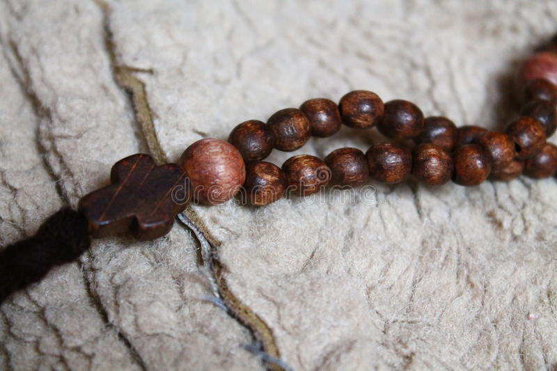 Rosary. Beautiful wooden brown color rosery with little cross for count prayers stock photo