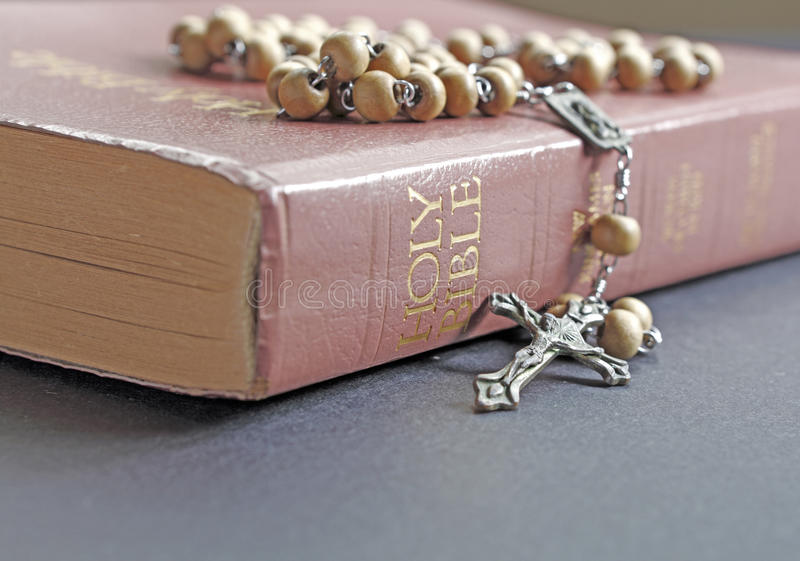 Rosary and Bible. Holy rosary beads with a crucifix on top of a Christian Bible stock photos