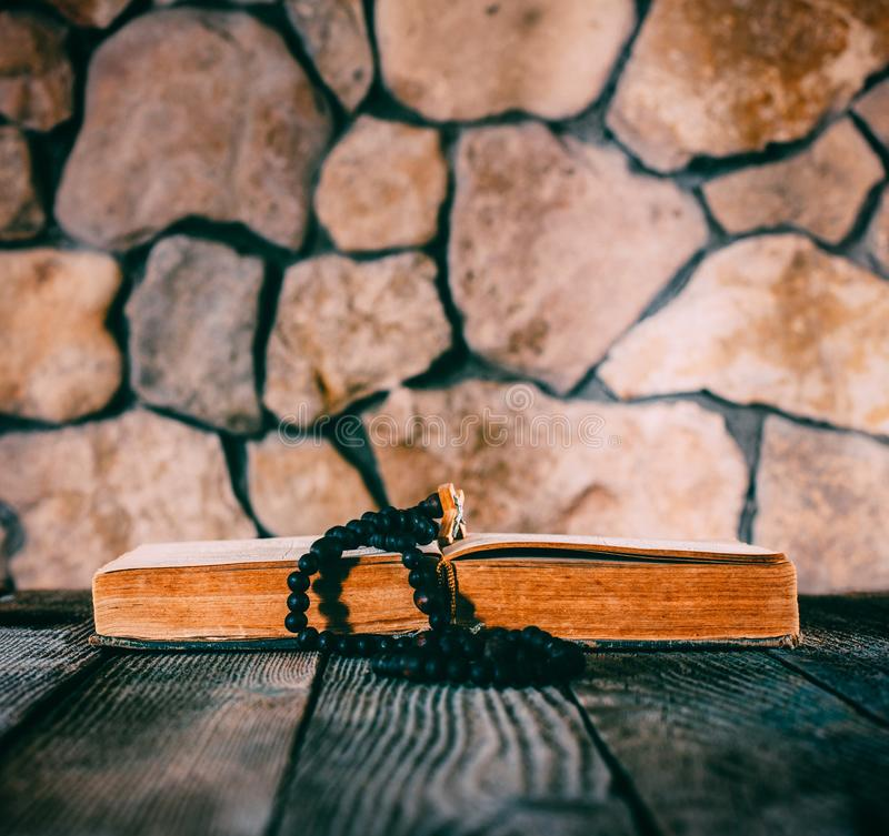 Rosary with a crucifix on an open old book on old wooden table on a background of stone walls royalty free stock image