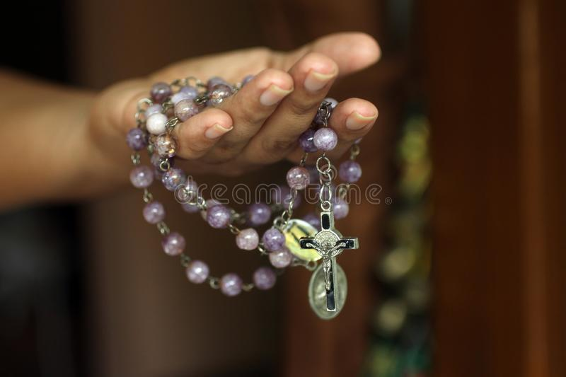 Rosary in one hand. Young junior lady holding rosary with open hand. Female hands holding a rosary with Jesus Christ Cross or royalty free stock image