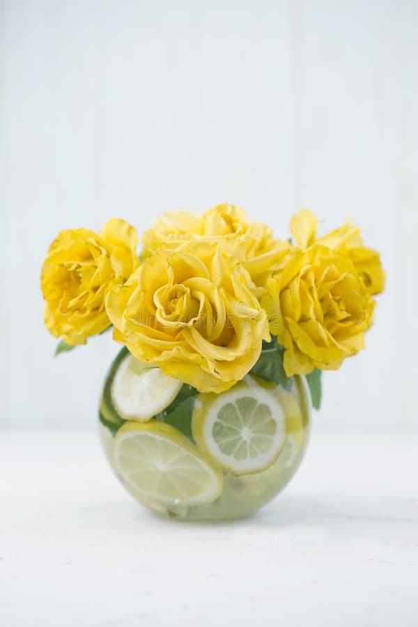 Rosas amarelas no vaso na tabela Feriados e conceito da celebra??o fotografia de stock
