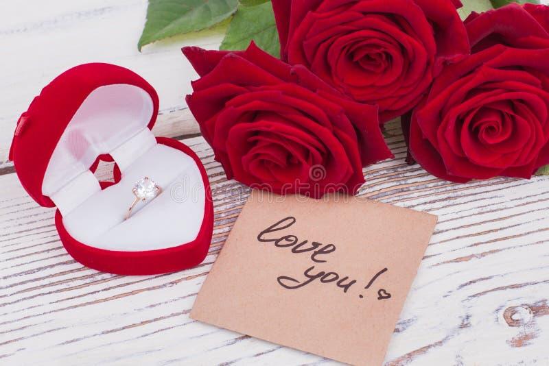 Rosas, anillo de diamante y mensaje del amor fotografía de archivo