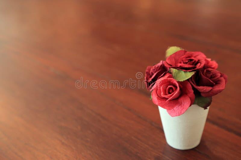 Rosas artificiales rojas en pequeño pote blanco en la tabla de madera con el espacio para el texto fotografía de archivo