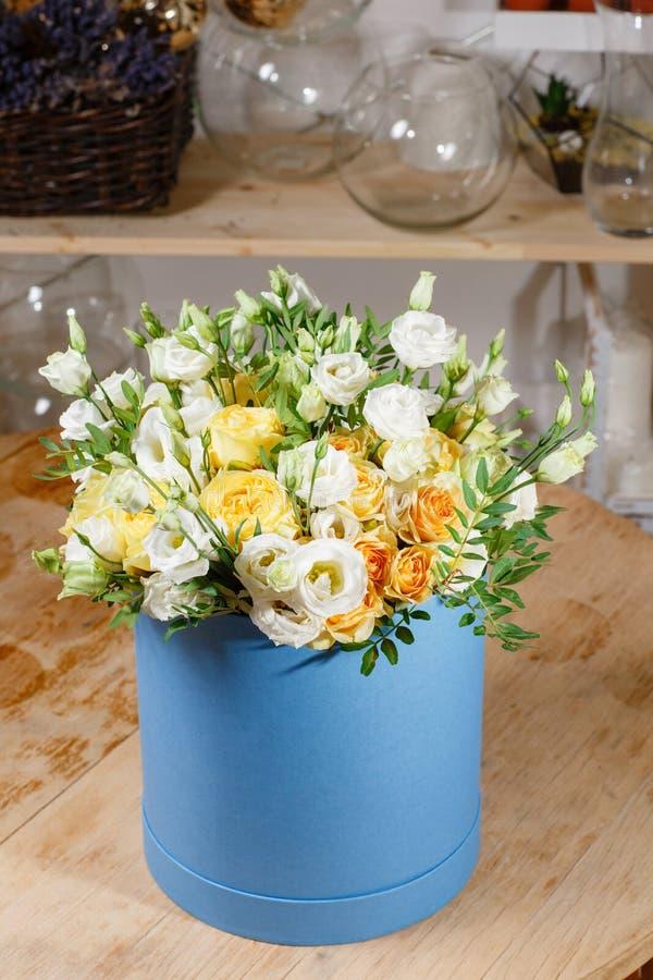 Rosas blancas y amarillas del eustoma rico del manojo de la composición en hatbox Una diversa mezcla de los colores de las flores imagenes de archivo