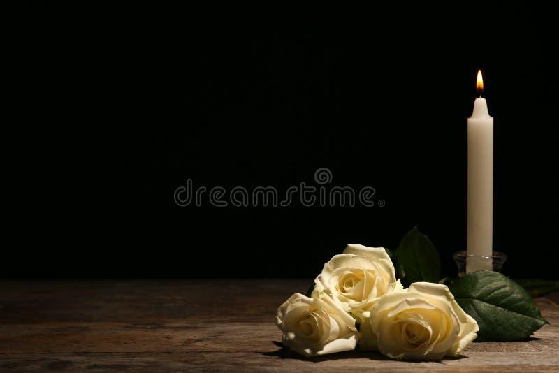 Rosas blancas y vela hermosas en la tabla contra fondo negro foto de archivo libre de regalías