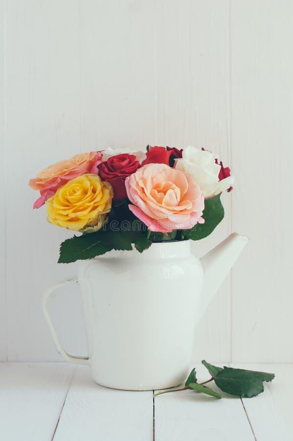 Rosas coloridas en el pote blanco del café del esmalte fotografía de archivo