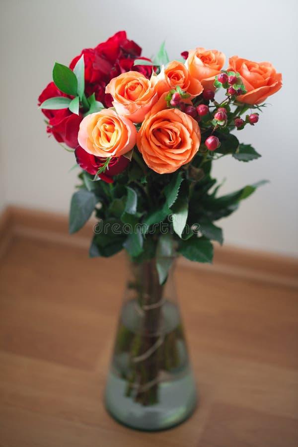Rosas coloridas en un florero en el fondo blanco foto de archivo