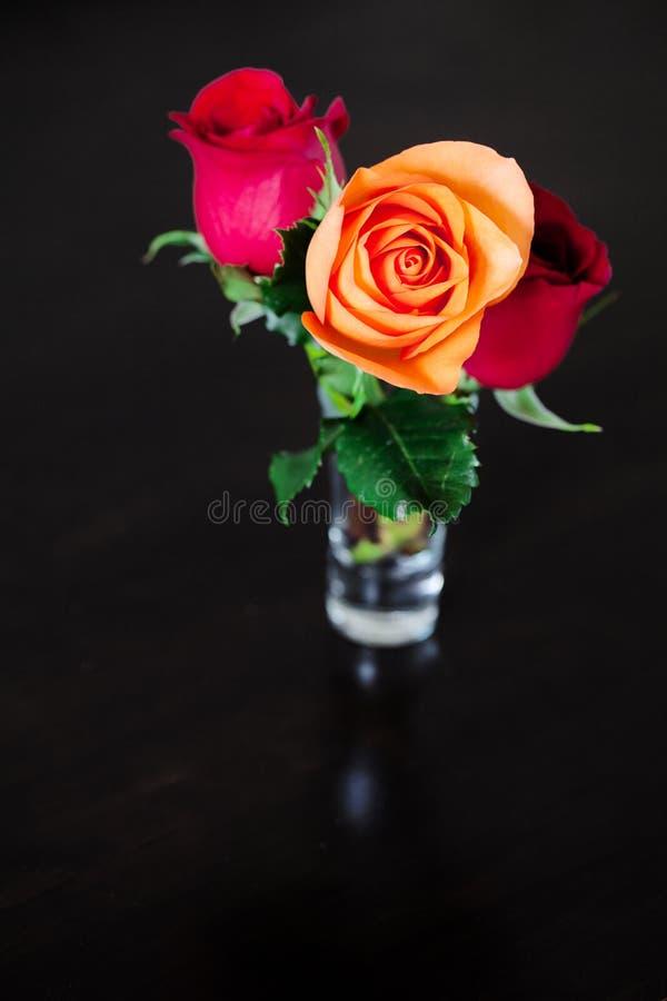 Rosas coloridas en un florero en un vector de madera fotografía de archivo libre de regalías