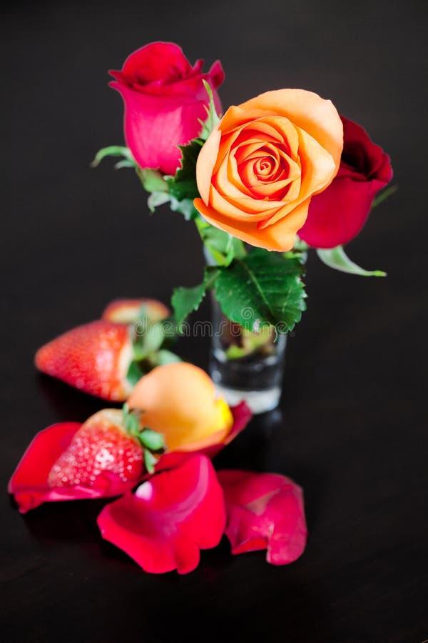 Rosas coloridas en un florero y una fresa en un vector de madera imágenes de archivo libres de regalías