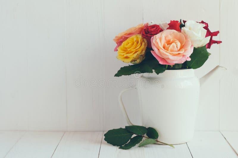 Rosas coloridas no potenciômetro branco do café do esmalte foto de stock