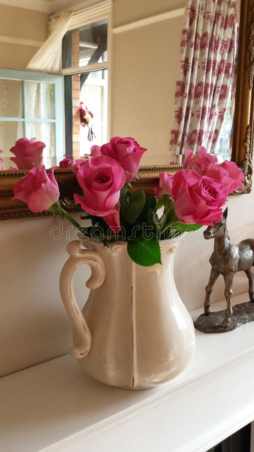Rosas cor-de-rosa bonitas em um jarro de creme fotos de stock