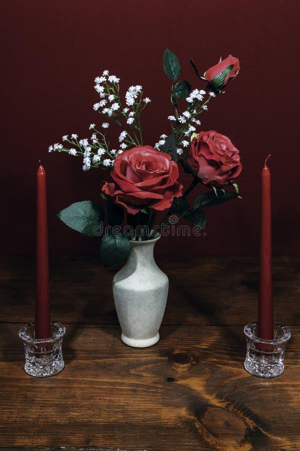 Rosas cor-de-rosa bonitas em um vaso acsented com as flores da respiração do bebê, duas velas vermelhas no suporte de cristal imagens de stock royalty free