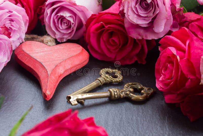 Rosas cor-de-rosa de florescência com coração vermelho fotografia de stock