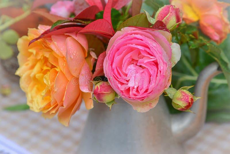 Rosas cor-de-rosa e amarelas em um bule do metal em uma tabela foto de stock royalty free