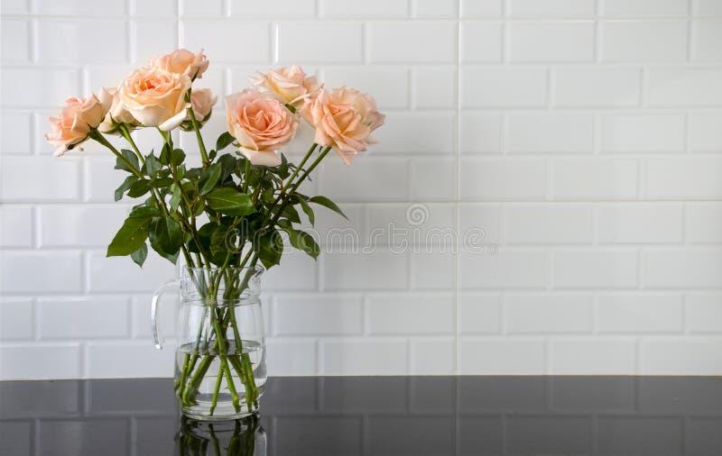 Rosas da cor do pêssego em um jarro de vidro fotografia de stock royalty free