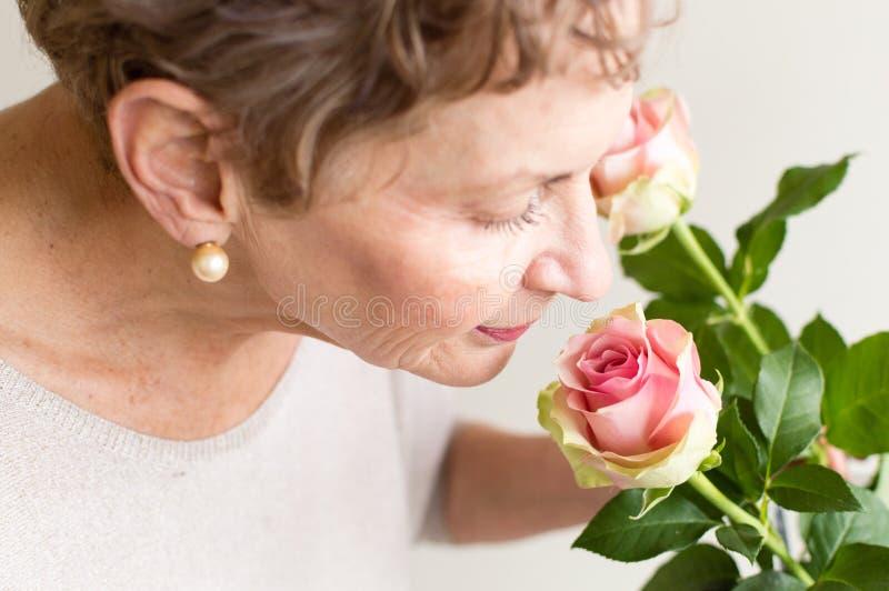 Rosas de cheiro da mulher mais idosa imagens de stock royalty free