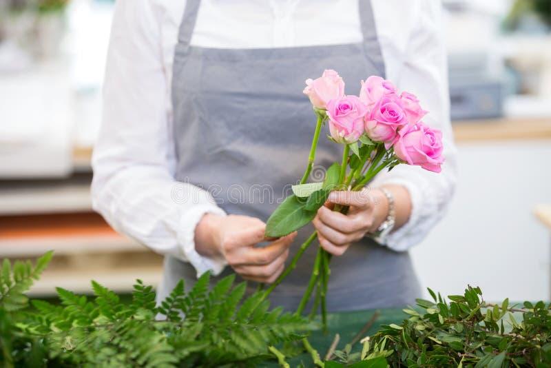 Rosas de Making Bouquet Of do florista no florista fotografia de stock