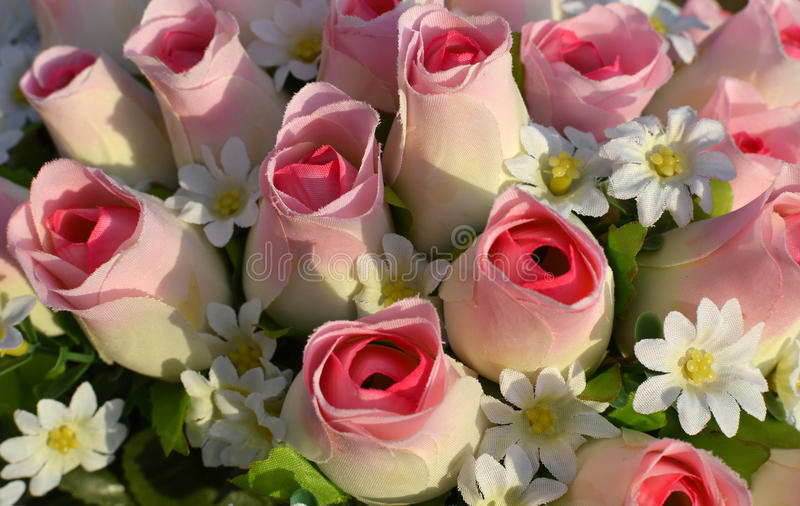 Rosas de seda y flores blancas. foto de archivo
