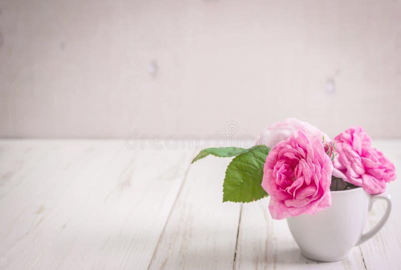 Rosas de té rosado en un fondo de madera blanco imágenes de archivo libres de regalías