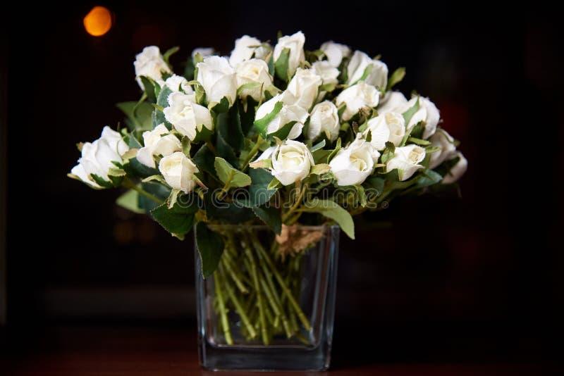 Rosas decorativas brancas em um vidro em um fundo escuro fotos de stock royalty free