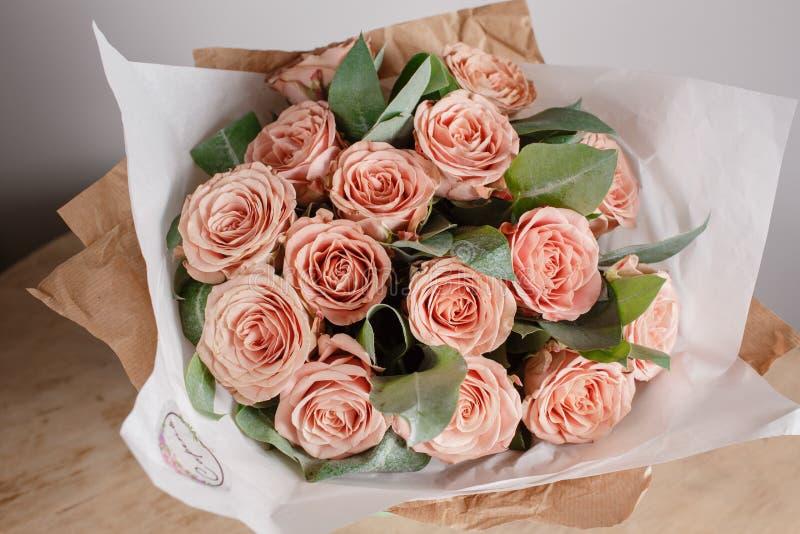Rosas del grado de Capuchino Muchacha del florista con las flores ricas del manojo Ramo fresco del resorte Fondo del verano Flor  fotografía de archivo libre de regalías