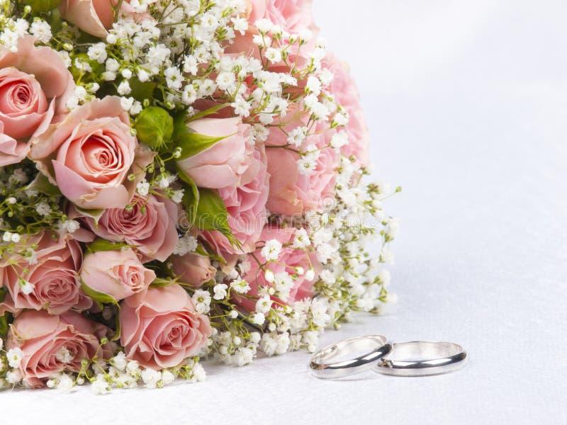 Rosas do ramalhete e anéis de casamentos fotografia de stock royalty free