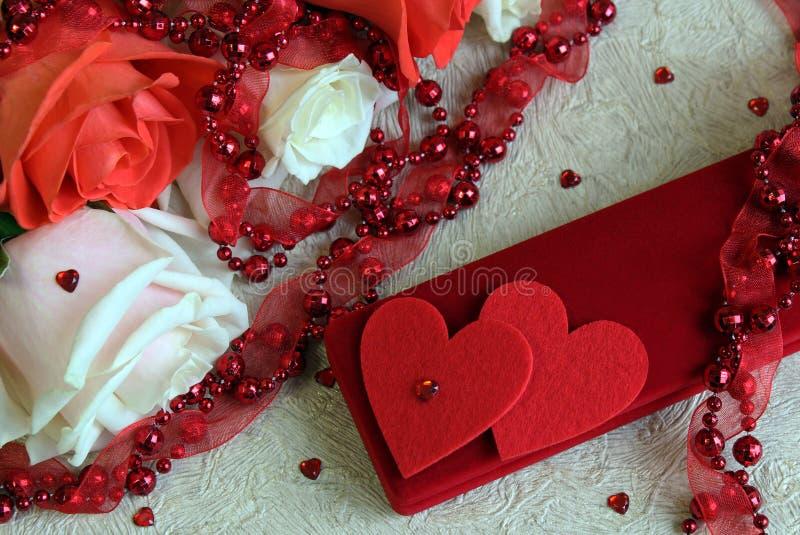 Rosas do rosa e as brancas, com grânulos vermelhos, dois corações e uma caixa com um presente, em um fundo claro para as felicita fotografia de stock