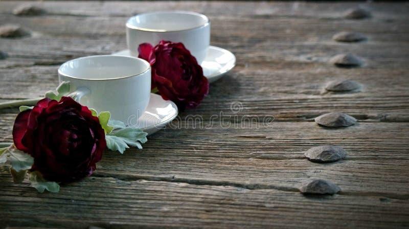 Rosas e chá, copo branco, estações foto de stock