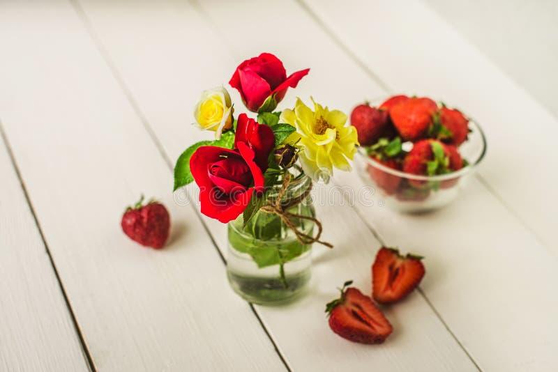 Rosas em um vaso de vidro na tabela de madeira imagem de stock royalty free
