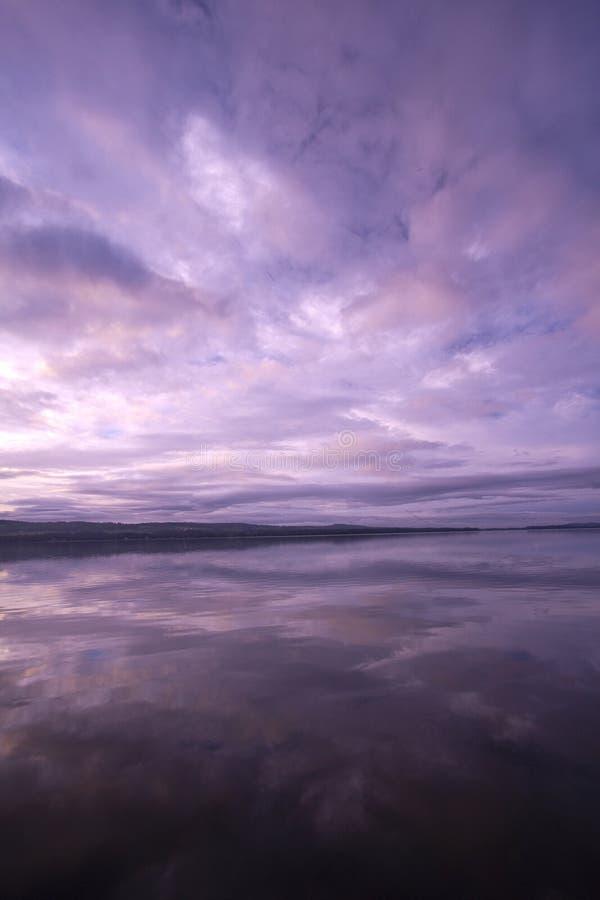 Rosas en colores pastel y púrpuras brillantes en salida del sol sobre las aguas inmóviles del lago Carmi en Franklin, VT, los E.E fotografía de archivo libre de regalías