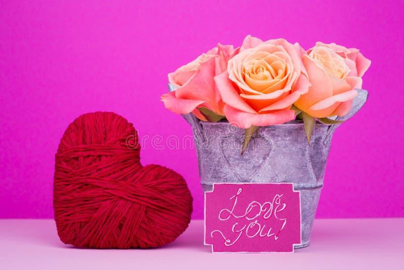Rosas en el pote, corazón, amor de la tarjeta usted fotos de archivo